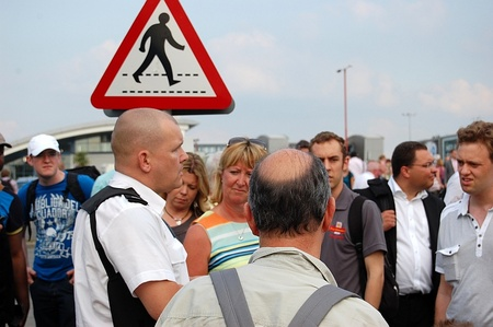 A police officer (left) attempts to explain the situation to frustrated passengers.