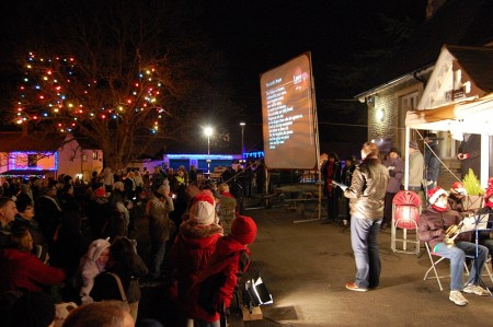 Stoke Gifford Carols on the Green - with screen displaying lyrics.