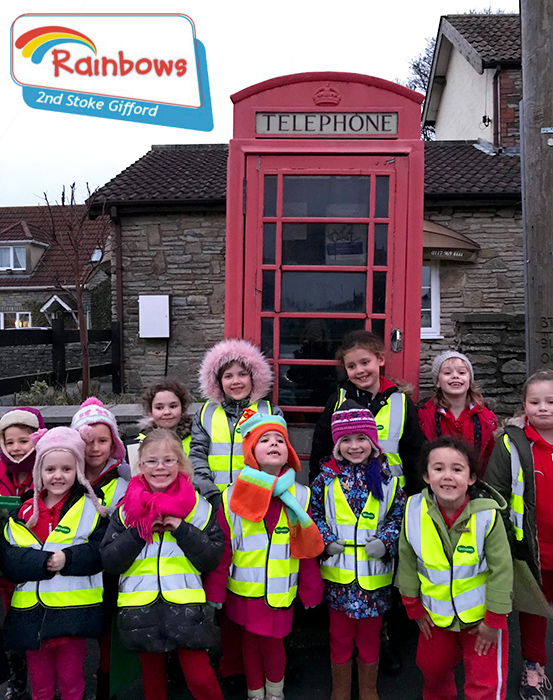 Photo of girls from the 2nd Stoke Gifford Rainbows gathered outside the disused telephone box.