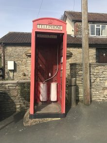 The telephone box without its door, which has been removed for repair.