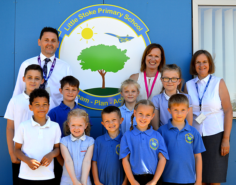Photo of staff and pupils at Little Stoke Primary School standing in front of a sign depicting the school logo.