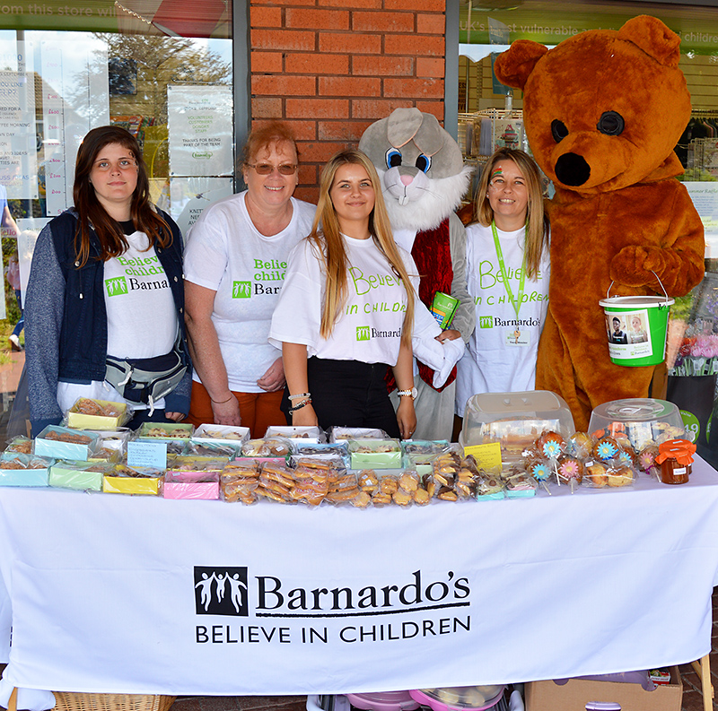 Photo of staff standing behind a table of cakes at the Barnardo's charity fun day.