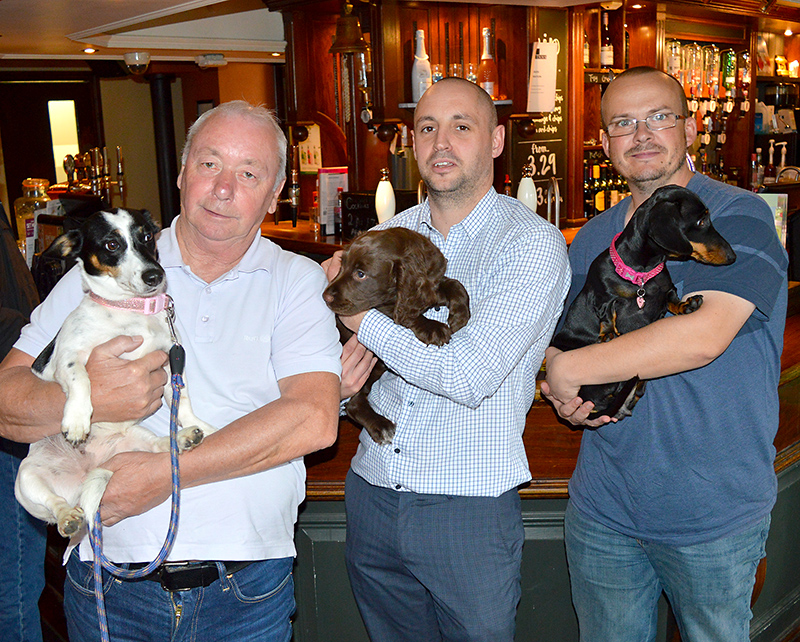 Photo of three dog owners standing in front of the bar and holding their pets in the Beaufort Arms, Stoke Gifford.