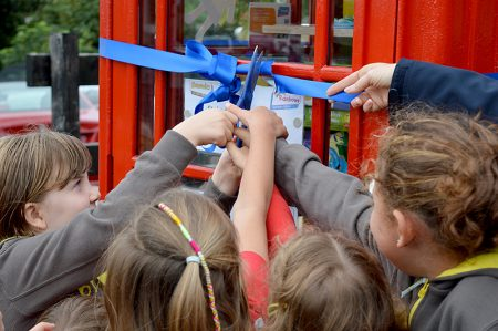 Photo of a group of rainbows jointly cutting a ribbon to officially open the toy library.