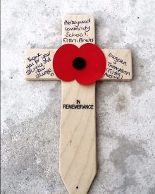 Photo of the annotated cross left beside Duncan J Thompson's name on a memorial at Tyne Cot cemetery.