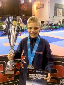 Photo of Liam Holden with trophy and medal.