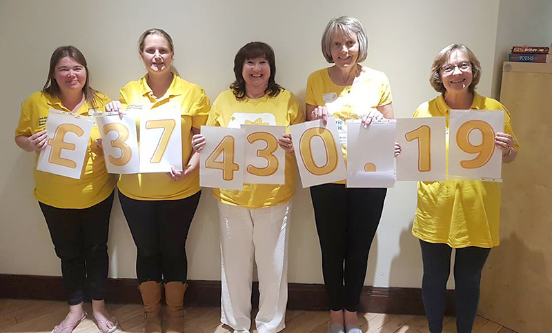 Photo showing members of the Marie Curie Five Stokes Fundraising Group holding up cards showing the amount they have raised since 2014.