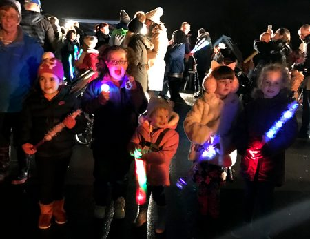 Photo of children holding various lighted toys at the fireworks display.