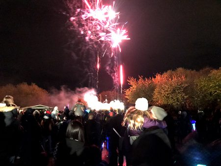 Photo of a crowd of people watching the fireworks display.