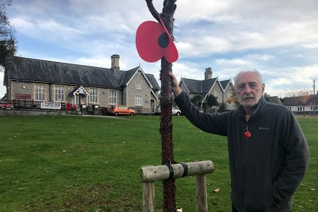 Photo of Adrian Kerton with one of the giant Remembrance poppies he installed.