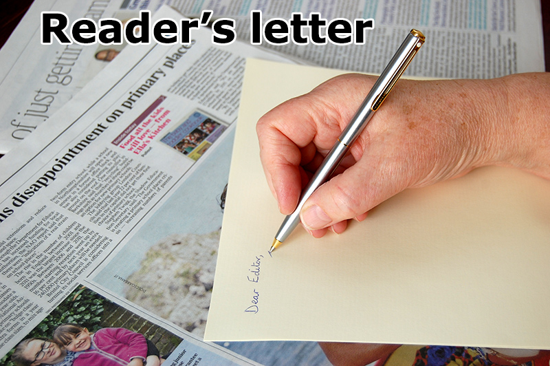 Photo of a pen in the hand of someone writing a letter.