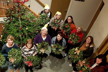 Photo of participants in the wreath-making event, each holding their finished wreath.