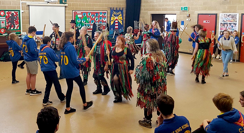 Photo of Scouts being taught morris dancing by a visiting side.