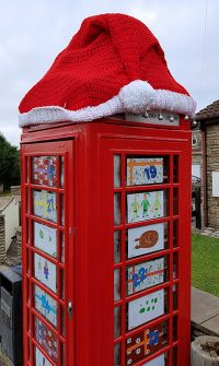 Photo of the toy library topped with a yarn-bombed Santa hat.