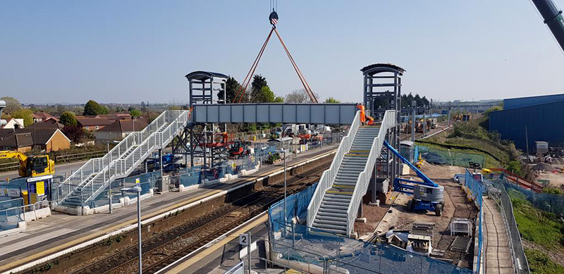 Photo of the deck of the new footbridge being lifted into position by a crane