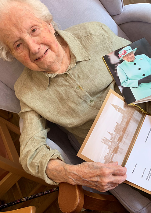 Photo of Rosa Hunter holding her 100th birthday greeting from the Queen.