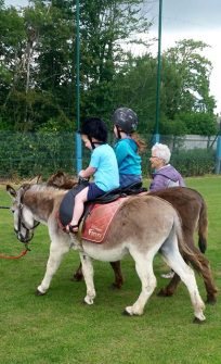 Photo of two children riding donkeys.