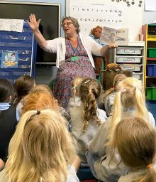 Photo of Ali Smith reading one of her stories to some of the Reception class children.