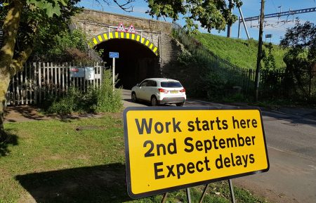 Photo of a 'Work starting here soon' sign at the railway bridge.