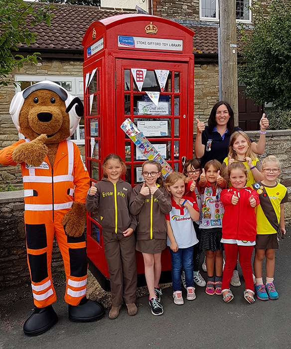 Photo of Charlie Critical Care Bear with members of 2nd Stoke Gifford Rainbows and Brownies in front of the toy library.