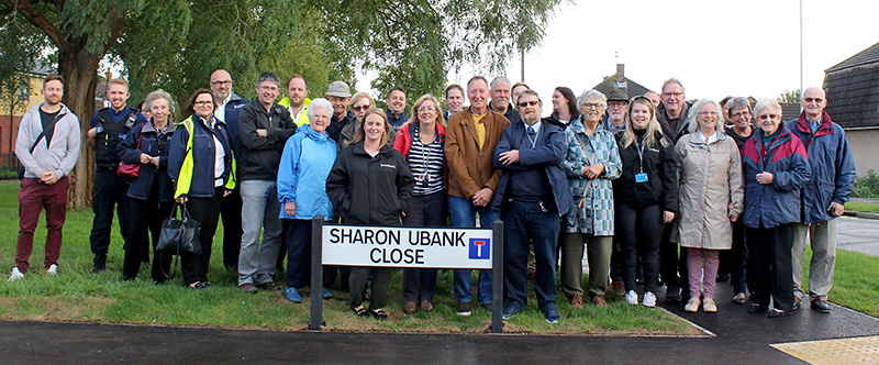 A crowd gathered around the road sign for Sharon Ubnak Close at the official opening.