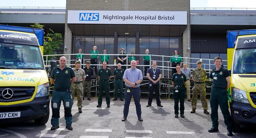 Photo of paramedics, ambulance teams, army personnel and hospital staff standing in front of NHS Nightingale Hospital Bristol.