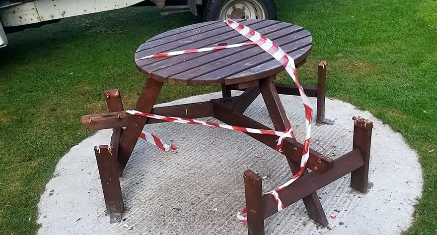 Photo of a vandalised picnic table and bench.