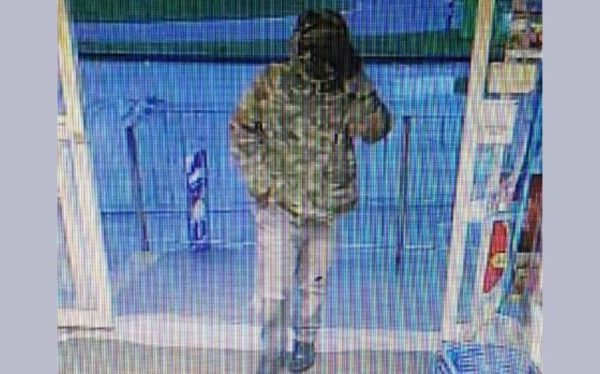 CCTV image showing a masked person entering the store.