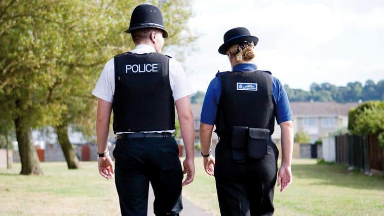 Photo (from behind) of a PCSO and a police officer walking along a path.