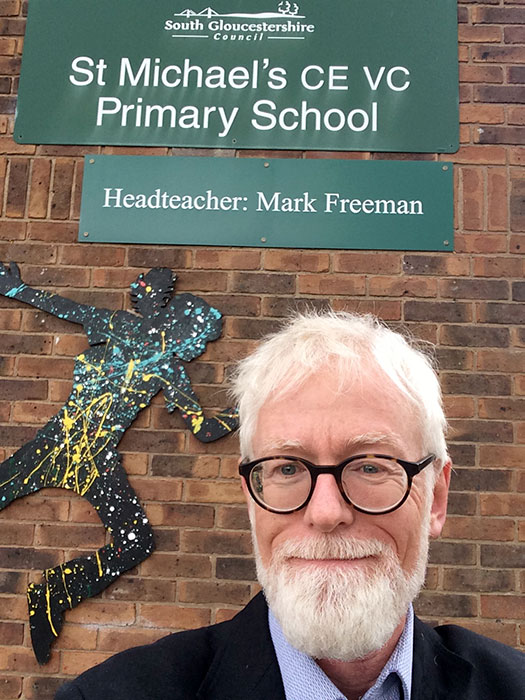 Photo of a man, with a school sign behind him.