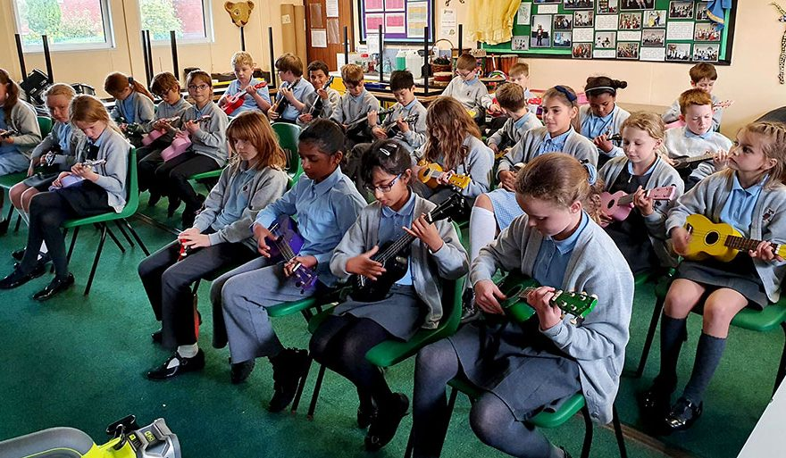 Photo of a classroom of children playing ukulele.