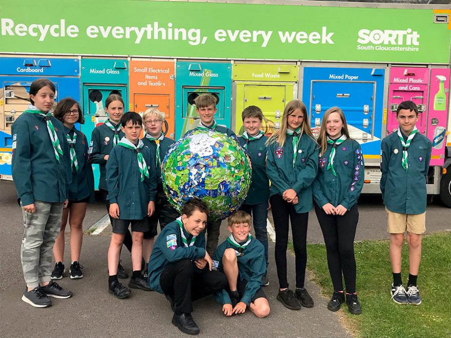 A group of Scouts standing in front of a recycling collection truck.
