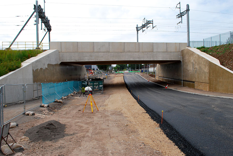 Photo of a partly-tarmacked road under a bridge.