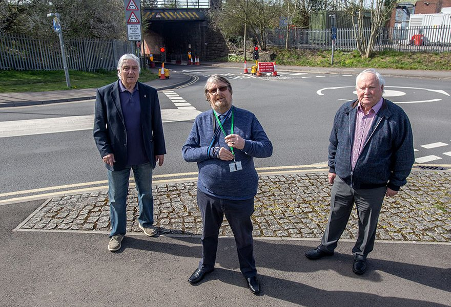 Photo of three people standing in front of a bridge.