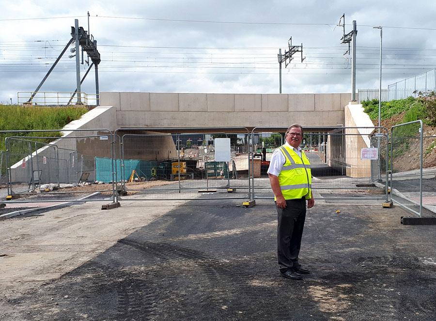 Photo of a man in hi-vis vest standing in front of a bridge.