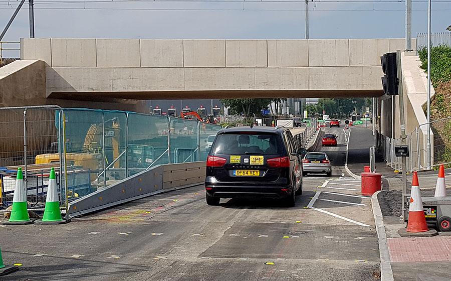 Photo of cars passing under a bridge.
