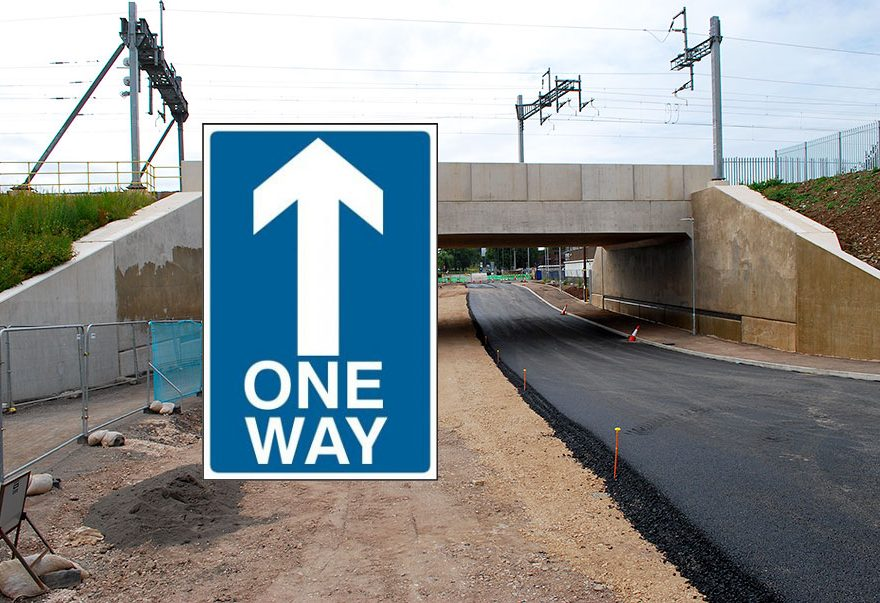 Composite image of a one-way road sign over a photo of a railway bridge.