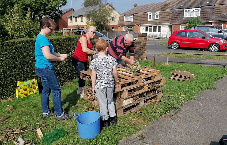 Photo of a group of people building a bug house.