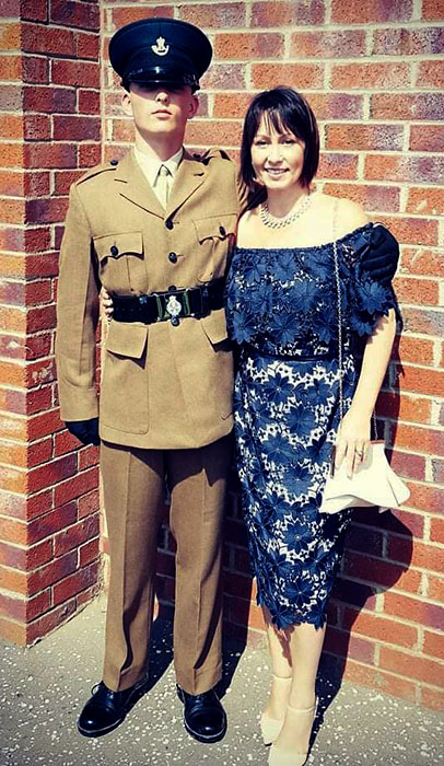 Photo of a soldier in uniform and a lady in a dress.