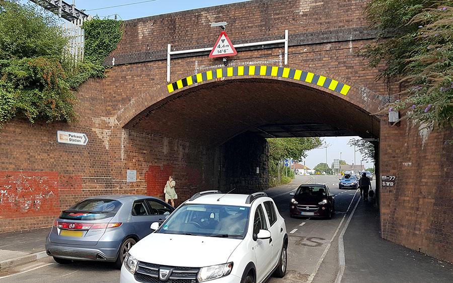 Photo of traffic passing under a railway bridge.