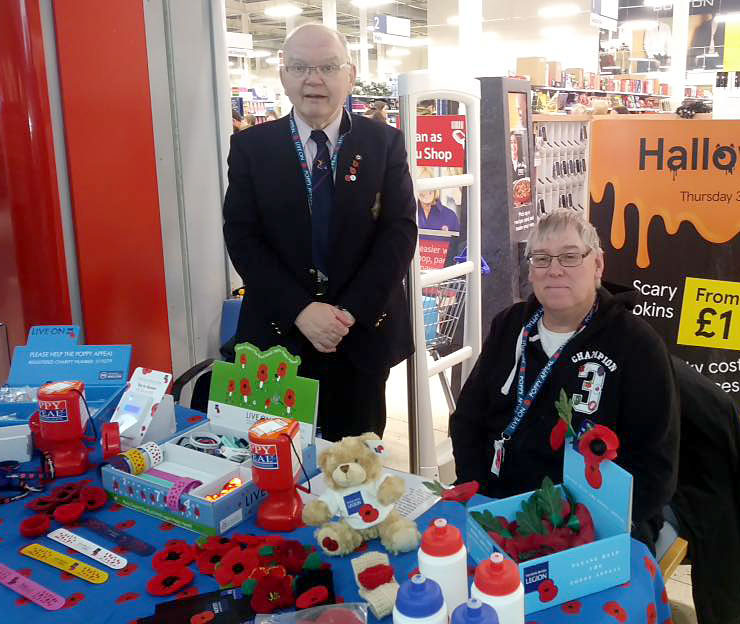 Photo of two Poppy Appeal collectors behind a table.